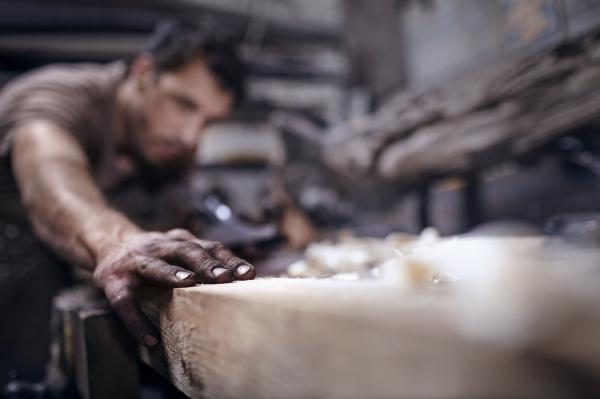 craftsman chiseling wood in workshop