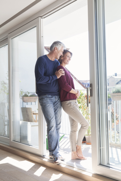smiling couple leaning against balcony door