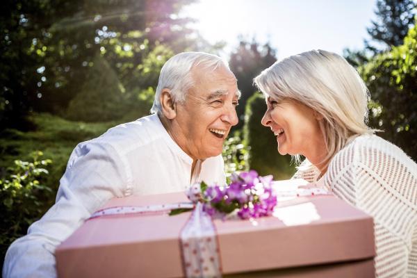 happy elderly couple with large present