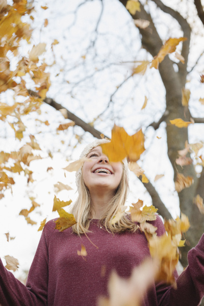 a teenage girl outdoors throwing autumn