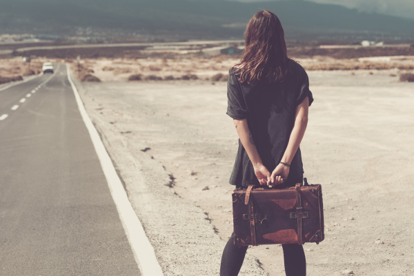 young woman with suitcase walking on