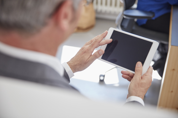 mature man using digital tablet in