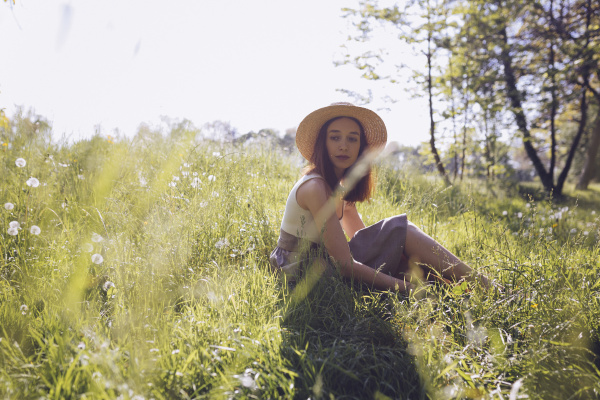 young woman wearing straw hat sitting