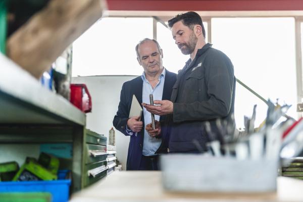 engineers with digital tablet in workshop