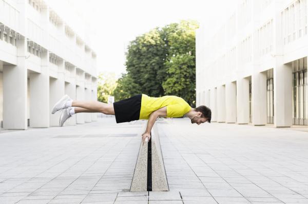 young man balancing horizontally on divider