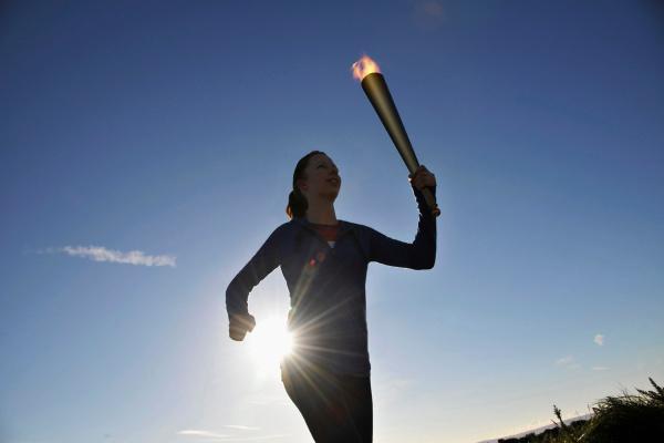 athlete running with flaming baton