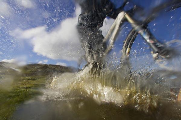 mountain biker riding through a puddle