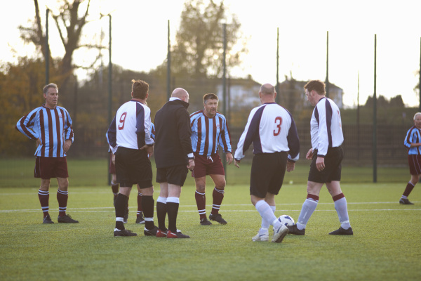 referee and football players settling dispute