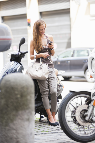 mid adult woman leaning against scooter