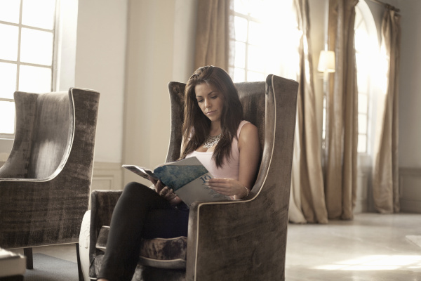 woman sitting in chair reading magazine