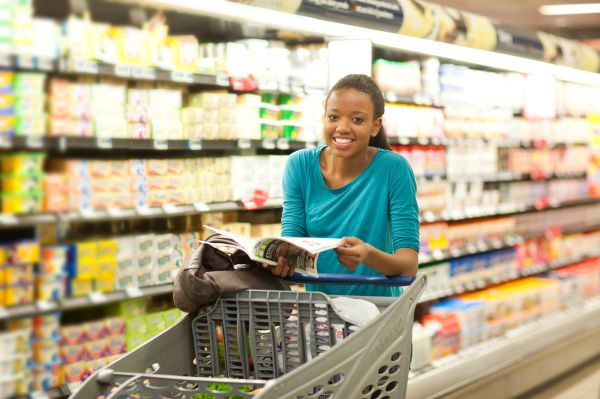 female shopper with brochure in supermarket