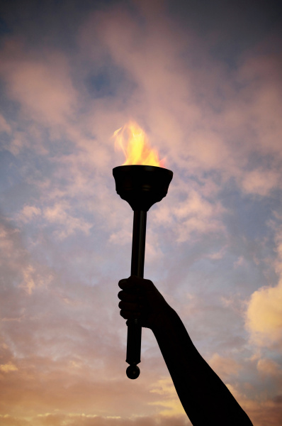 hand holding flaming baton