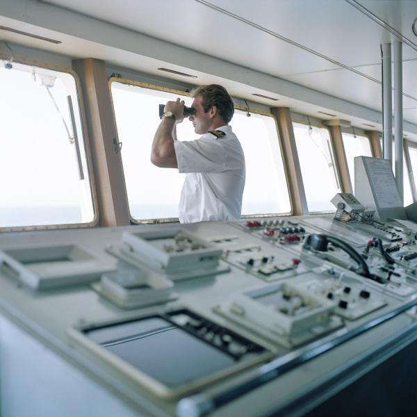 sailor using binoculars on container ship
