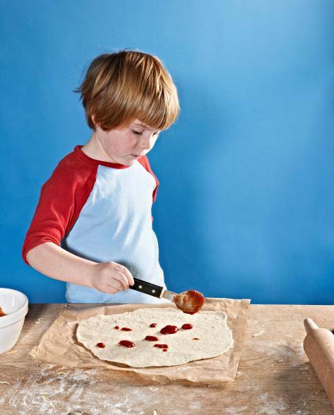boy spreading sauce on pizza dough
