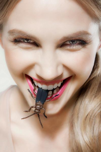 young woman biting plastic beetle