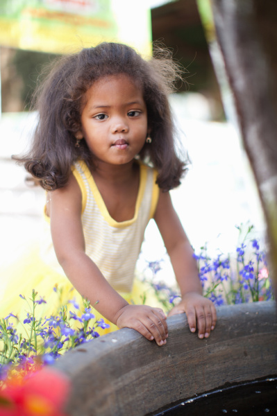 girl leaning on edge of planter
