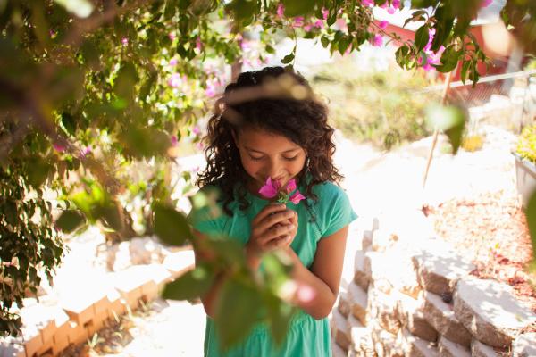portrait of girl in garden smelling