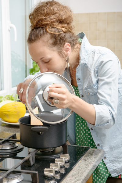 young woman cooking dinner in the