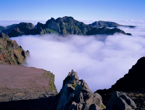 clouds below mountain peaks pico do