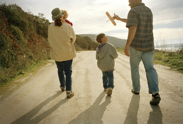two parents walking with their young