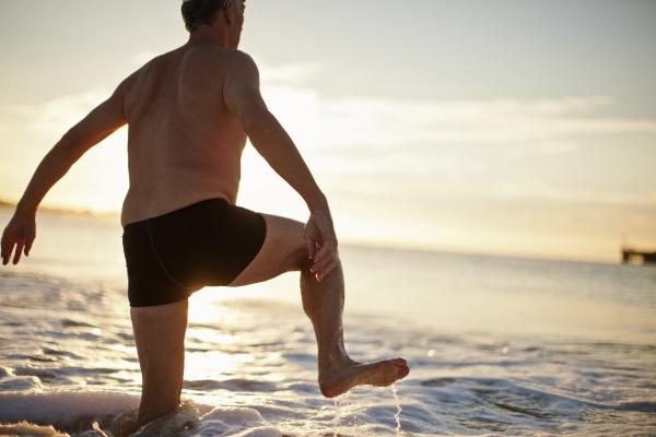 senior man wading in the ocean