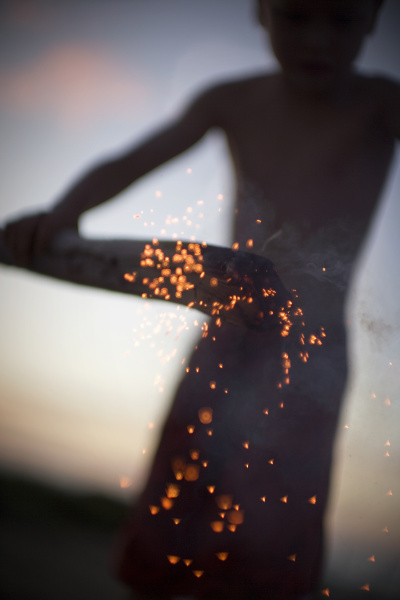 embers spraying from a burning stick