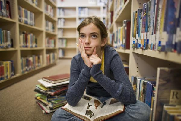 thoughtful teenage girl reading books in