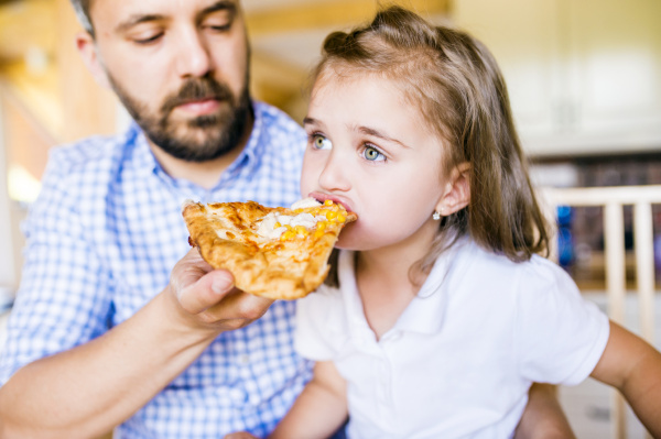 father feeding his little daughter with
