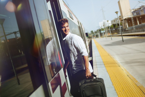 young man with suitcase entering a