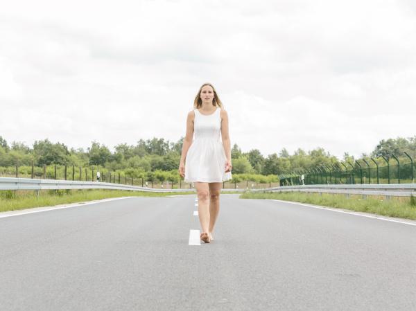 young woman in white dress walking