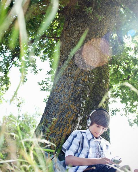 boy in headphones leaning against tree