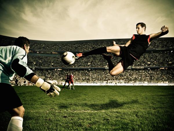 football player hits ball at goal