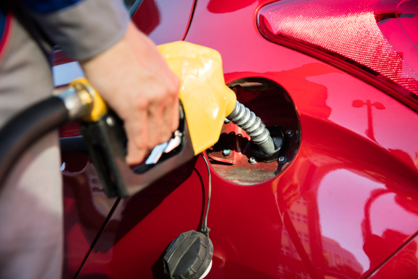 persons hand refueling cars tank