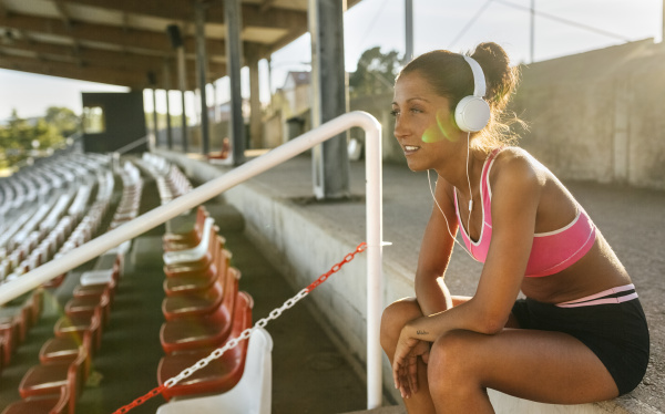 female athlete taking a break listening