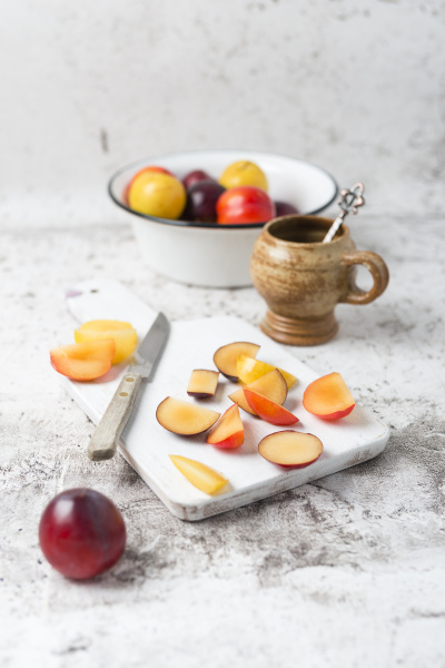 various plums in bowl chopping board