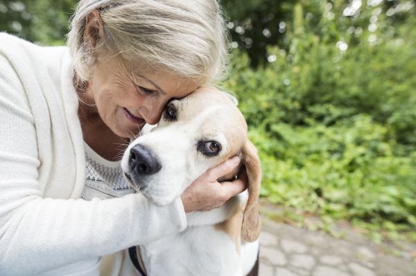 happy senior woman cuddling her dog