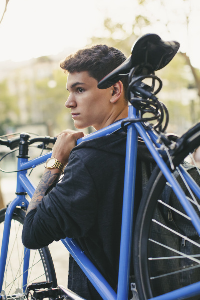 teenager carrying fixie bike in the
