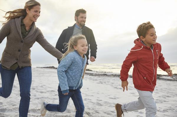 playful family running on winter beach