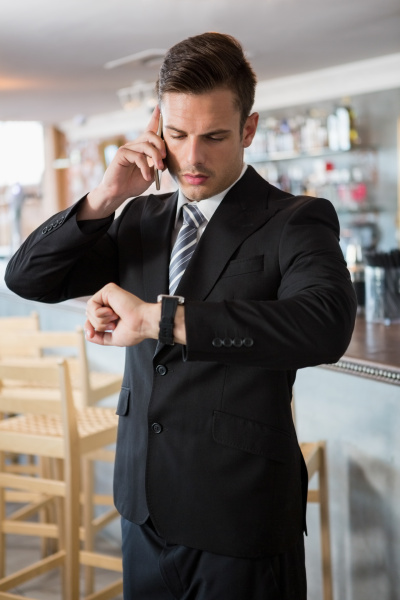 businessman checking time while talking on