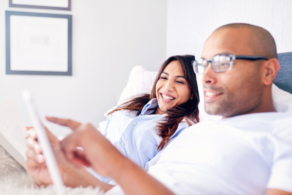 smiling couple using digital tablet on