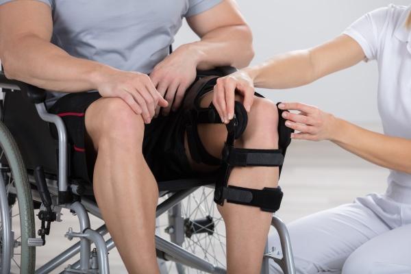 physiotherapist fixing knee braces on man