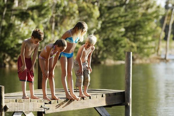 children in swimwear standing on jetty
