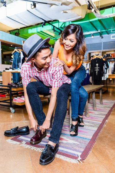 asian couple buying shoes in store