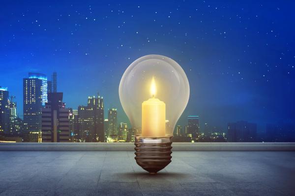 burning candle inside light bulb on