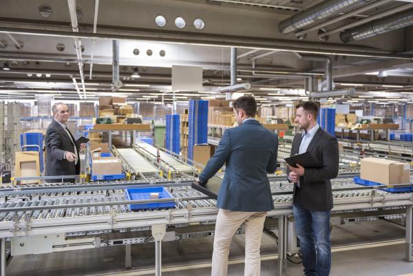 three businessmen at conveyor belt in