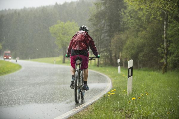 man rides a bike up a