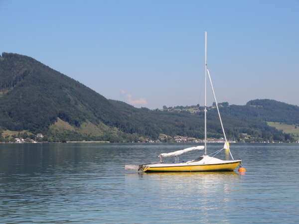 yellow sailboat on blue lake with