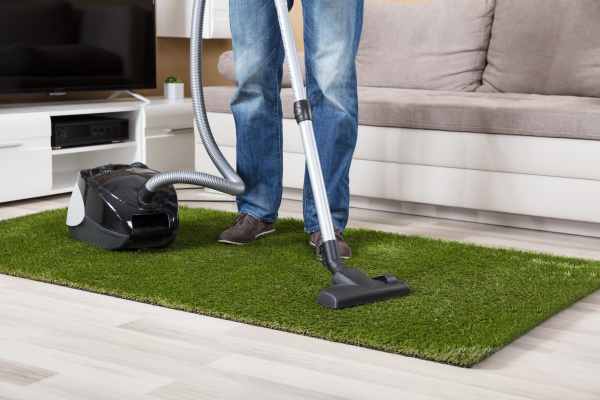 person cleaning green carpet with vacuum