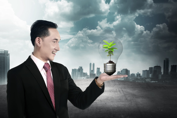business person holding light bulb with
