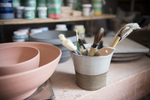 pottery brushes and bowls in workshop